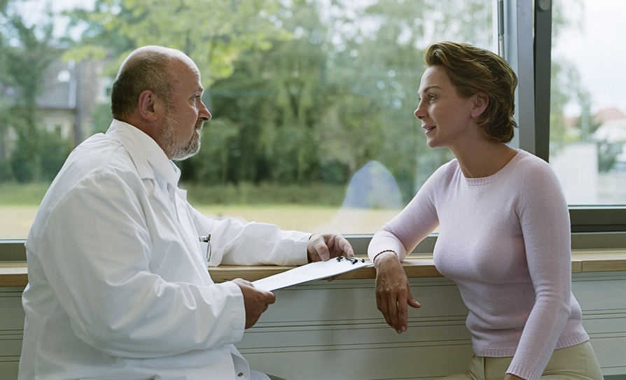 doctor talking with patient at window